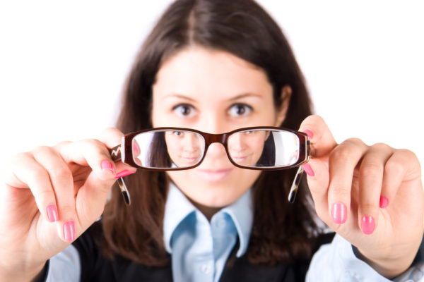 Young woman looking through eyeglasses. Isolated on white.